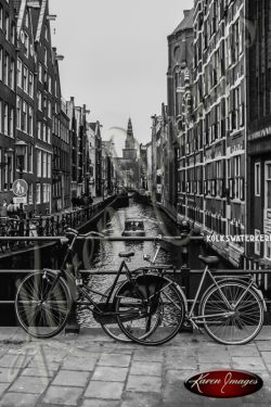 bike locked to canal guard black and white amsterdam holland