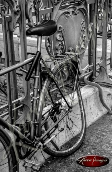 black and white of bicycle chained to metro station railing